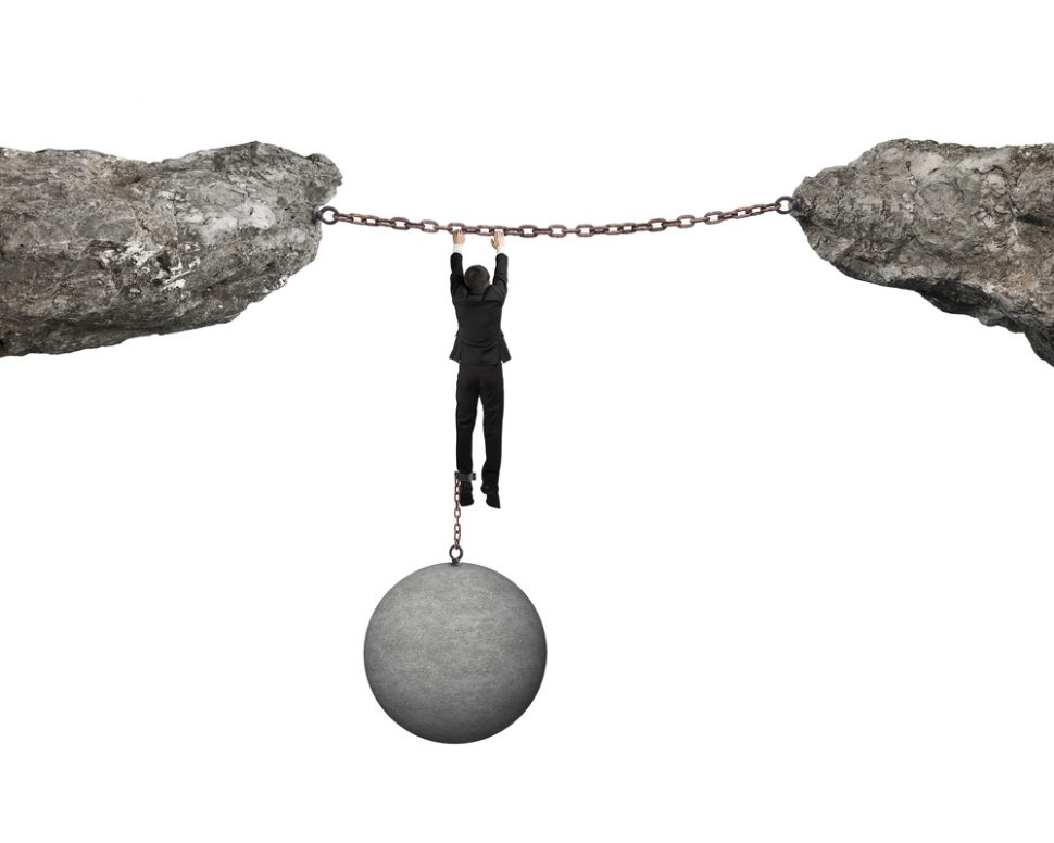Businessman shackled by ball hanging on iron chains link cliffs, Impact of a Job Loss on Alimony, Spousal or Child Support Modification