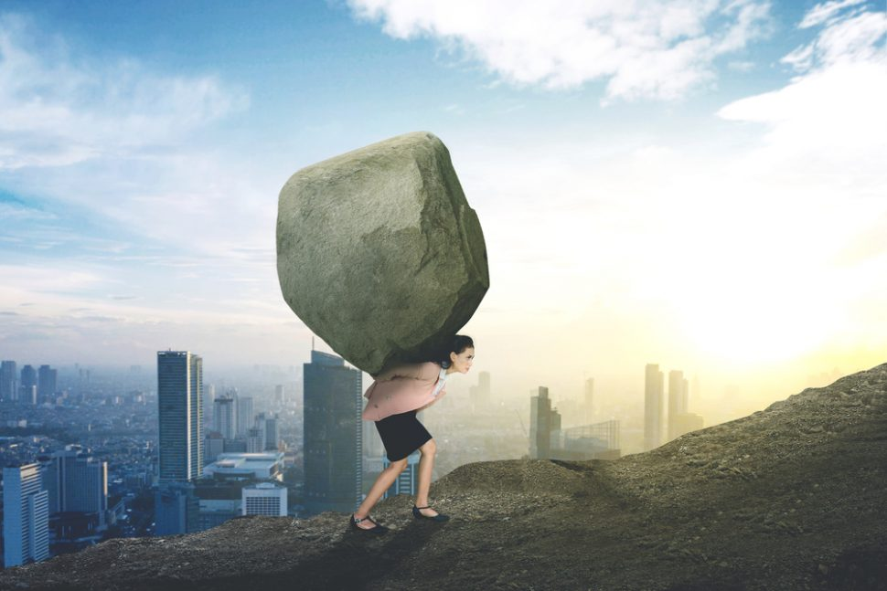 Caucasian businesswoman lifting stone on the hill
