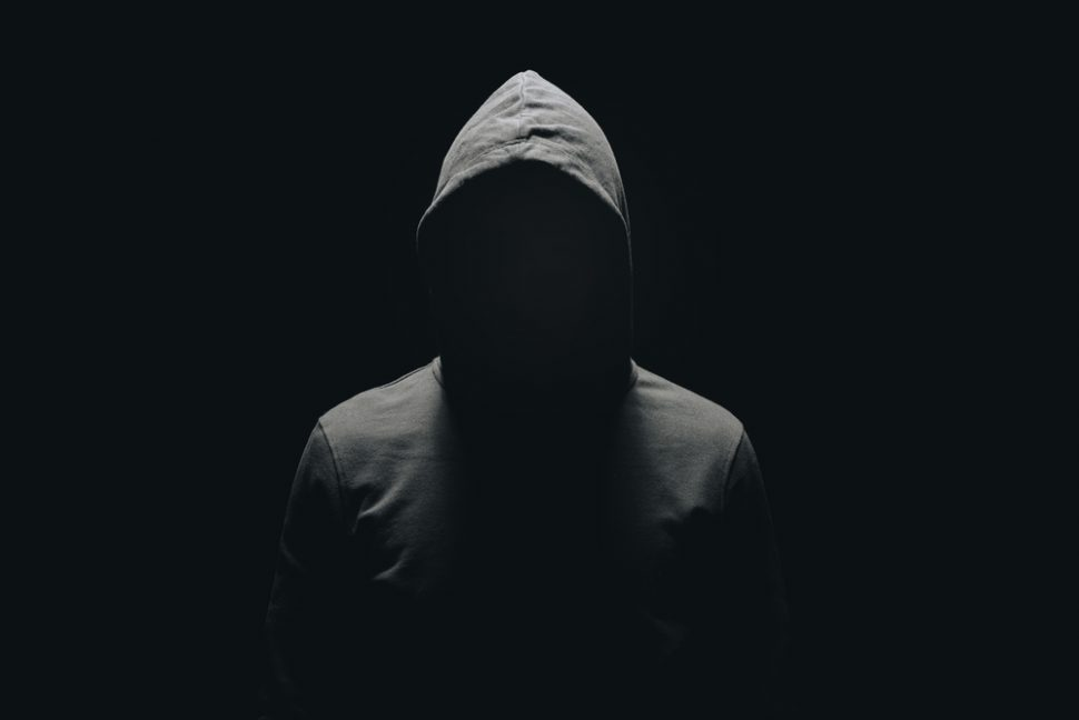 Human figure wearing a hoodie in shadow