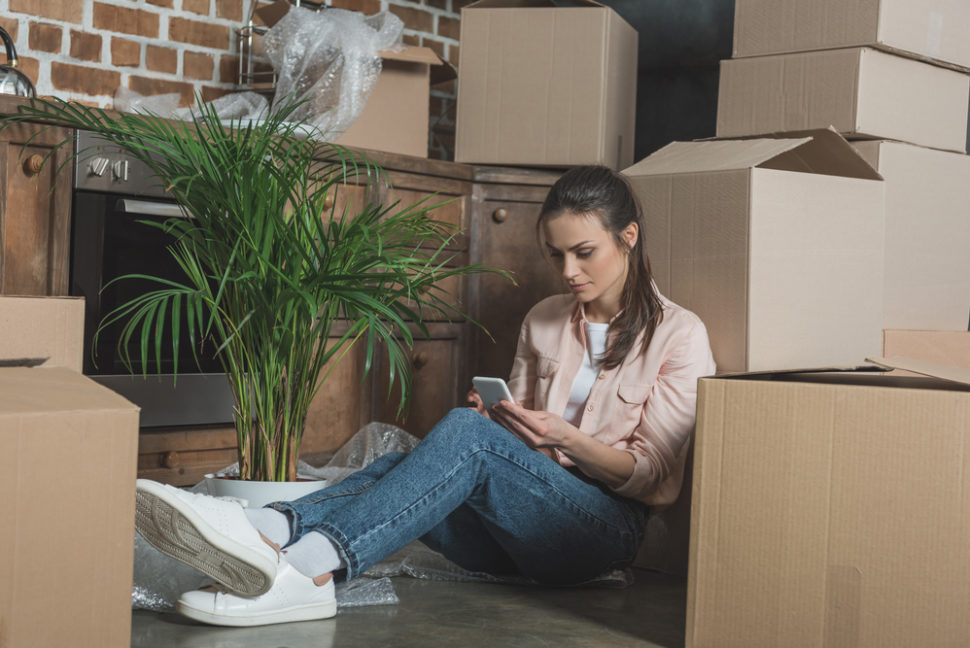 Young woman using smartphone while sitting between cardboard boxes in new apartment