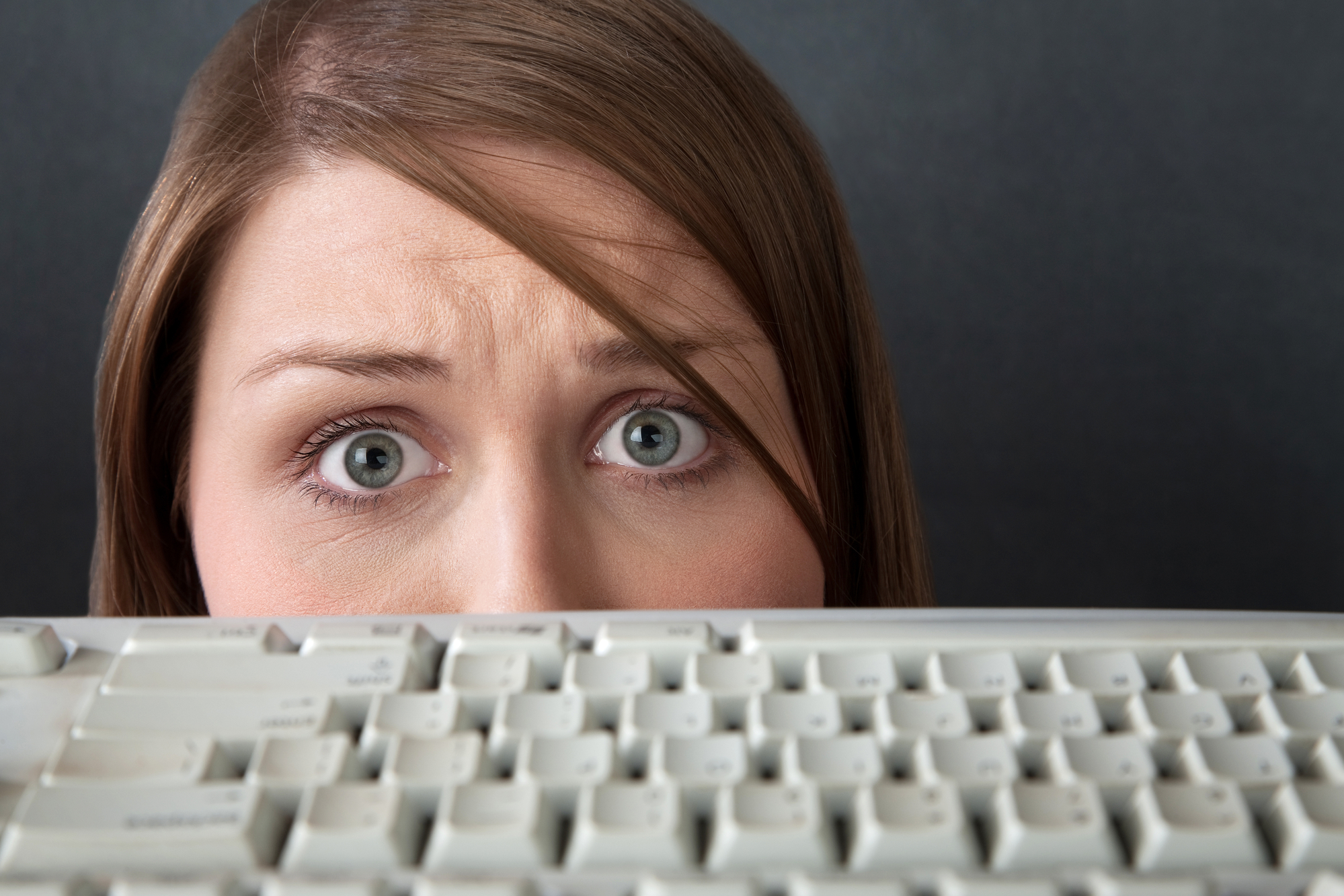 Nervous wide-eye Caucasian woman in front of a computer keyboard