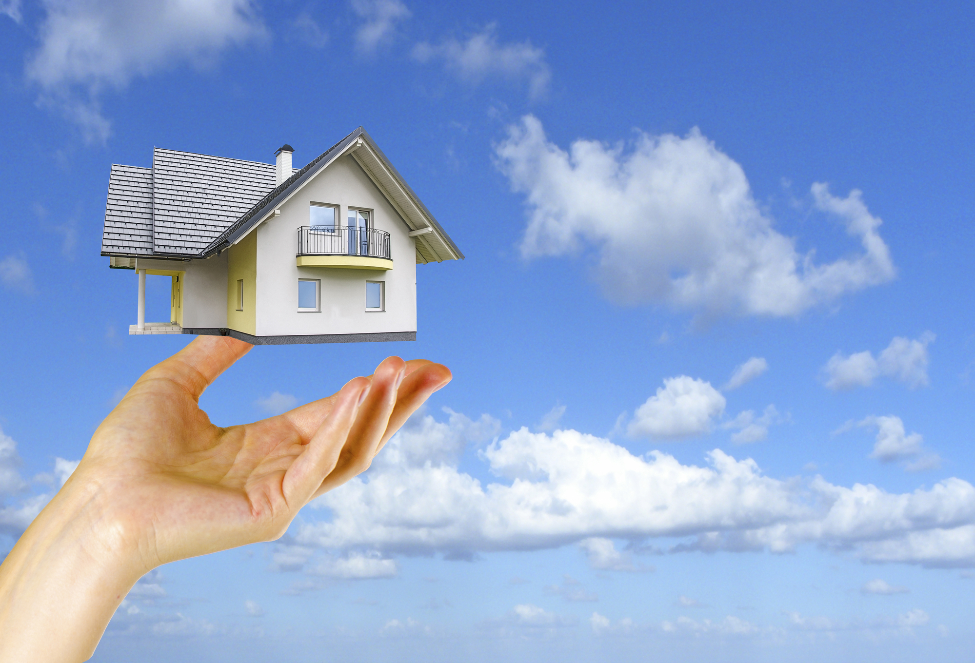 Outstretched hand with home hovering above with a blue sky in the background