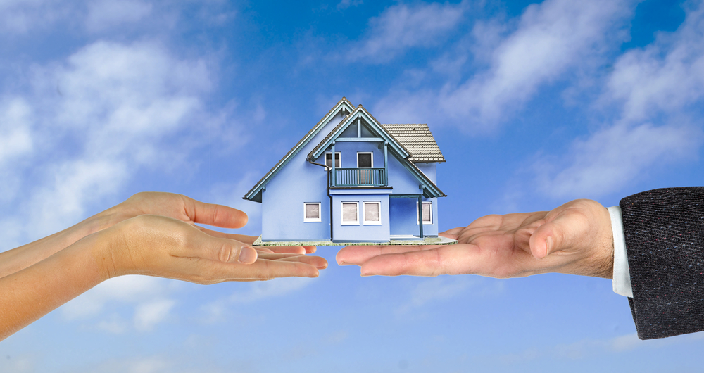 one hand giving the gift of a house to another hand all on the background of a blue sky with wispy clouds