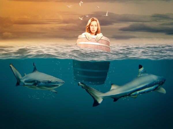 Woman floating in a barrel with sharks swimming around her