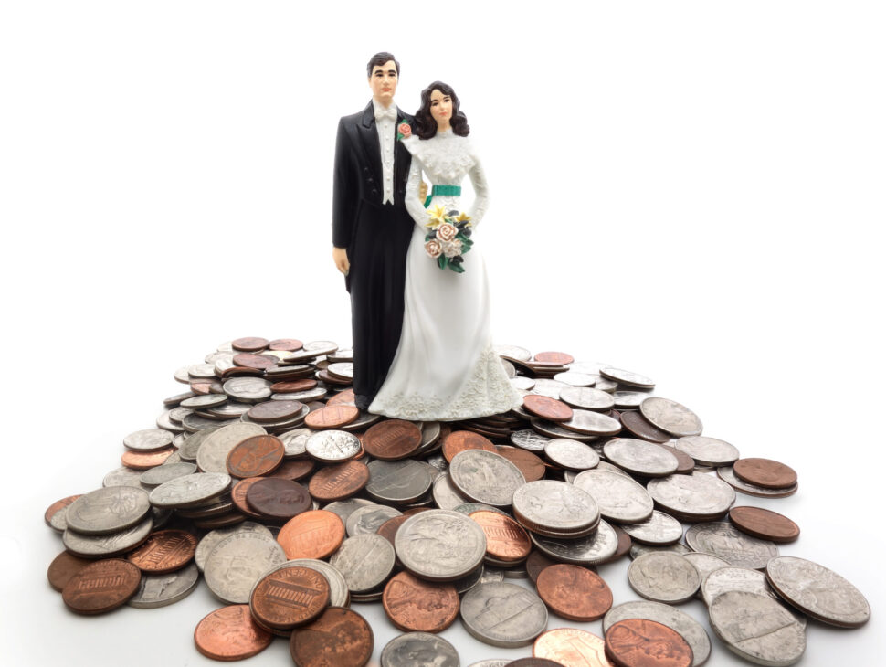 Plastic wedding couple on a pile of coins - money concept